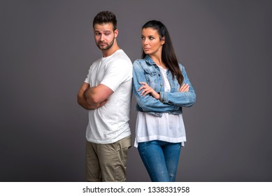 A beautiful young couple standing back to back and feeling upset to each other