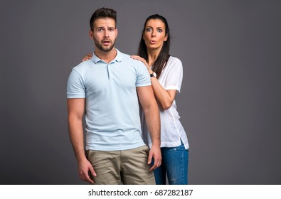 A beautiful young couple standing and feeling scared in a studio