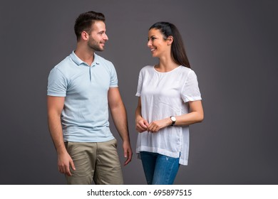A beautiful young couple standing and laughing in good mood