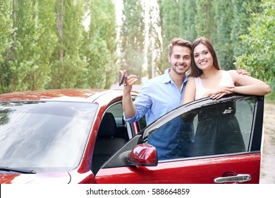 Beautiful young couple standing near red car with keys