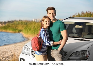 Beautiful young couple standing near car outdoors