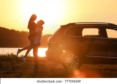 Beautiful young couple standing near car