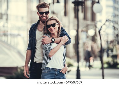 Beautiful young couple in sun glasses hugging, looking at camera and smiling while standing outdoors