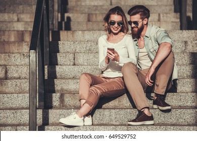 Beautiful young couple in sun glasses is using a smart phone and smiling while sitting on stairs outdoors