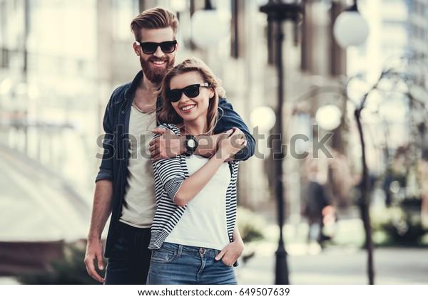 Bel jeune couple de lunettes de soleil se tenant dans ses bras, regardant la caméra et souriant tout en se tenant à l'extérieur