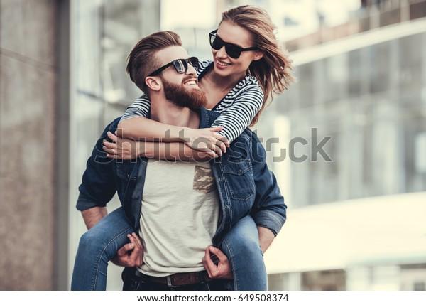 外に立ちながら互いを見つめ合い微笑む、サングラスをかけた美しい若い夫婦。子豚