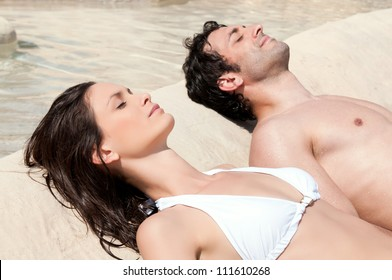 Beautiful young couple sunbathing together in summer