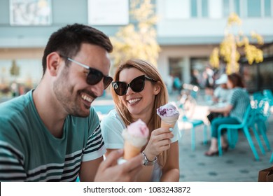 A beautiful young couple with sunglasses are sitting outdoors and having ice-creams in cornet