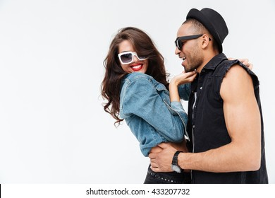 Beautiful young couple in sunglasses smiling and hugging together over white background