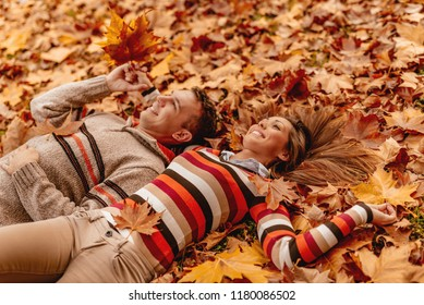 Beautiful young couple in sunny forest in autumn colors. They are lying on the ground covered with fallen leaves and enjoying.