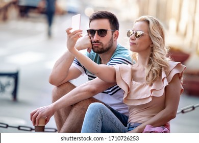 Beautiful young couple taking a selfie with a smartphone in the city.