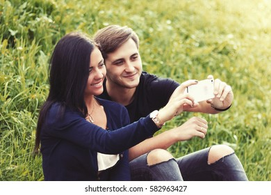 Beautiful young couple  taking selfie outdoors.