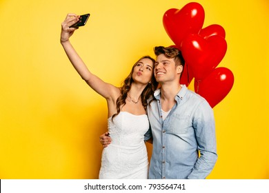 Beautiful young couple taking selfie on mobile phone, standing on yellow background with red balloons, dressed in jeans shirt and white dress, celebrating Valentine's day.