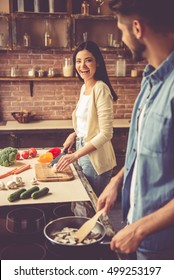 Beautiful young couple is talking and laughing while cooking in kitchen at home