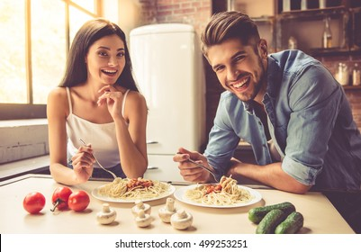 Beautiful young couple is talking, looking at camera and smiling while eating in kitchen at home