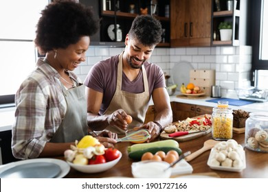 Beautiful young couple is talking and smiling while cooking in kitchen at home.