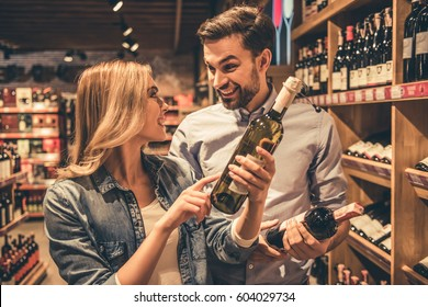 Beautiful young couple is talking and smiling while choosing wine at the supermarket