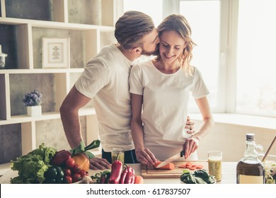 Beautiful young couple is talking and smiling while cooking healthy food in kitchen at home. Man is kissing his girlfriend in cheek