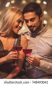 Beautiful young couple is tenderly touching with their heads, drinking wine and smiling during their date in a restaurant