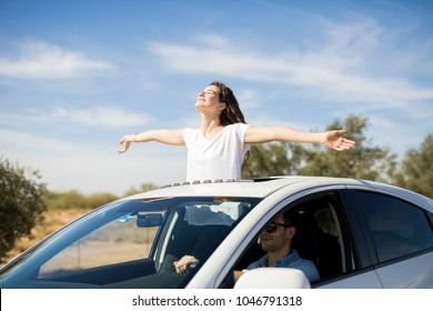 Beautiful young couple is travelling by car with girl standing out of the sunroof with arms outstretched
