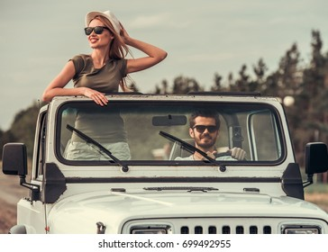 Beautiful young couple is travelling by car, girl is sticking out of the sunroof and smiling