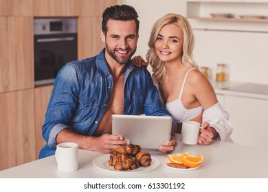 Beautiful young couple is using a digital tablet and smiling while having a breakfast in kitchen in the morning