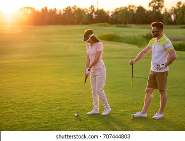 Beautiful young couple is using golf clubs while playing golf together