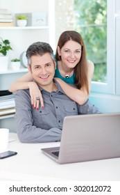 Beautiful young couple using laptop