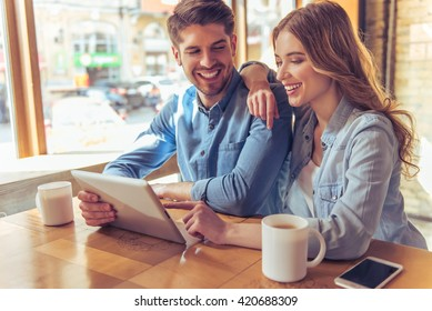 Beautiful young couple is using a tablet, talking and smiling while sitting in the cafe