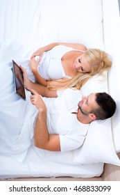 Beautiful young couple using a Tablet PC in Bed.