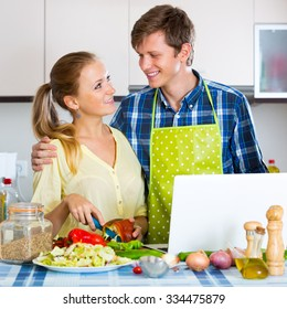 Beautiful young couple with vegetables and laptop in domestic kitchen