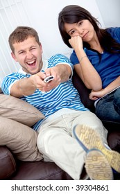 Beautiful young couple watching tv at home