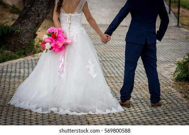 Beautiful Young couple with wearing a wedding dress  standing on the cement floor. And hold hands.
