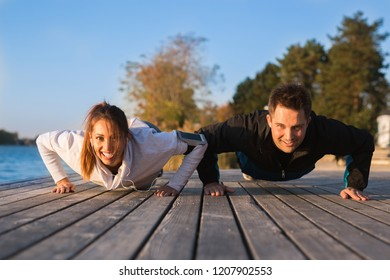Beautiful young couple working out outside doing push ups