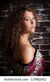 Beautiful young curly hair woman wearing sexy dress on brick wall background. Fashion portrait.