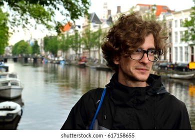 Beautiful young curly-haired guy in black-rimmed glasses travel in Europe on the background of the attractions in the Park, waiting for a date with a girl, resting, summer, spring