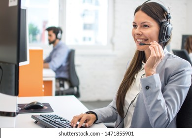 Beautiful young customer care operator with headset and microphone working in call centre