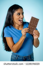 Beautiful young cute and happy latin woman in casual clothes holding big delicious chocolate tablet looking with temptation thinking if ignoring diet and eating sweet junk food isolated background