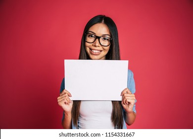 Beautiful young cute lovely asian woman in glasses with white blank board or banner in hands for advertisement over pink background