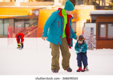 Beautiful young dad and his toddler boy, skiing in the mountains