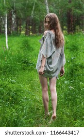 Beautiful young dirty mad and manic looking girl wearing torn clothes and smeared with mud and dried blood is walking with a knife in her hand in the forest. Copy space. Concept design.