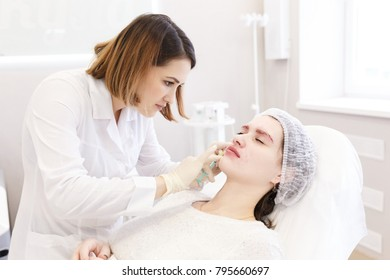 Beautiful young doctor cosmetologist doing filler injection in lips. Cosmetic Treatment. Plastic Surgery. Patient feels pain during Botox injections in lips. Real surgery