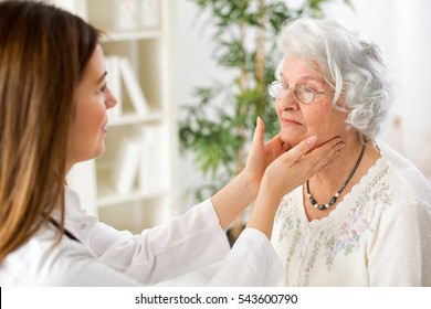 Beautiful young doctor examining senior woman lymph glands in ambulance