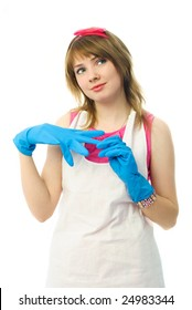 beautiful young dreamy housewife putting on blue rubber gloves and smiling