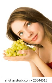 beautiful young dreamy woman holding grapes in her hands