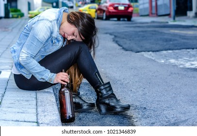 Beautiful young drunk woman sitting in a sidewalk with bottle of beer in her hand sleeping outdoor, desesperate woman and addict concept