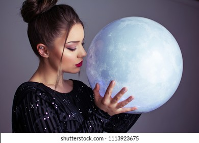 Beautiful young elegant woman holding a moon sphere ornament. Retouched, studio lighting, dark colors and moody feel.