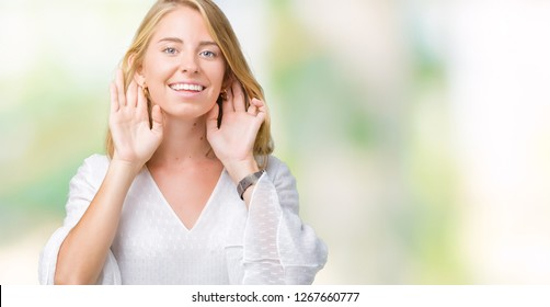 Beautiful young elegant woman over isolated background Trying to hear both hands on ear gesture, curious for gossip. Hearing problem, deaf