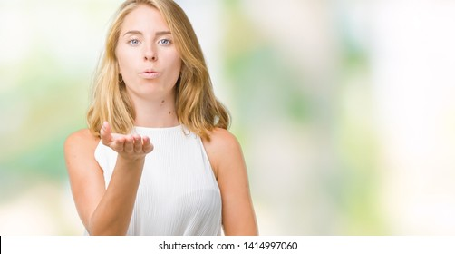 Beautiful young elegant woman over isolated background looking at the camera blowing a kiss with hand on air being lovely and sexy. Love expression.