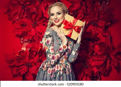 Beautiful young elegant woman in sexy red dress posing over red background with poinsettia holding present. Christmas photo
